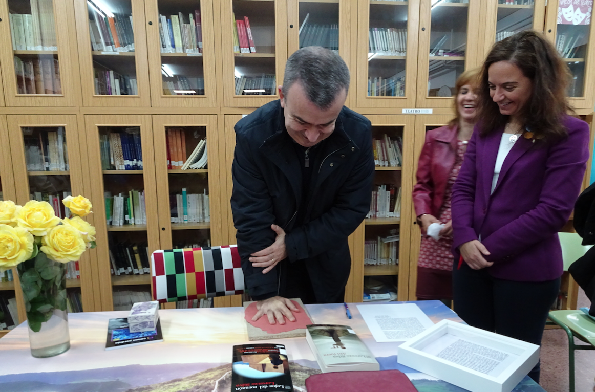 La alcaldesa de Getafe, Sara Hernández, y la profesora Yolanda Pérez observan el momento en el que Lorenzo Silva deja su huella para el paseo de la fama del IES La Senda